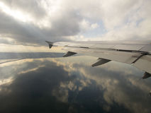 Flying. Over calm sea - reflections of blue seas,  skies and clouds Stock Images