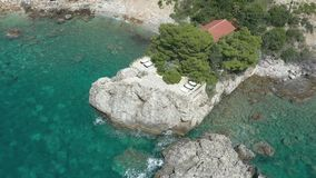 Flying over a cape. On which is seen a lonely house surrounded by coniferous trees. The turquoise sea washes the rocky coast of the cape and the sandy coastline stock footage