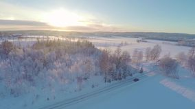 Flying over a car driving in winter landscape at sunset stock video footage