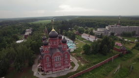 Flying over Cathedral of Ascension in Lukino, Russia. Aerial view of red brick Cathedral of Ascension built from 1890 to 1893 in Lukino Village, Russia stock footage