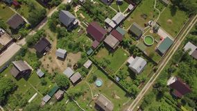 Flying over children in the pool and countryside houses, Russia. Aerial shot of boys bathing in outdoor pool with following panorama of dacha community and green stock video