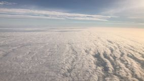 Flying over cirrus and cumulus clouds,4K video. Flying over cirrus and cumulus clouds, view through airplane window,view from a height in subdued light tones stock video footage