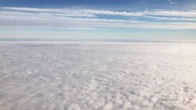 Flying over cirrus and cumulus clouds,video. Flying over cirrus and cumulus clouds, view through airplane window,view from a height in subdued light tones stock footage
