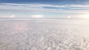 Flying over cirrus and cumulus clouds,video. Flying over cirrus and cumulus clouds, view through airplane window,view from a height in subdued light tones stock video