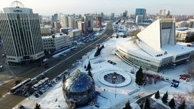 Flying over the city park in winter. spherical building. Car traffic stock video footage