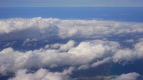 Flying over clouds above beach, view to skies from commercial airplane window