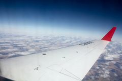 Flying over the clouds. The wing of the samlet and the beautiful sky. stock photos
