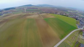 Flying over cultivated fields, green pastures, farmland. Agricultural industry stock video footage