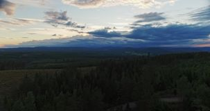 Flying over a dark forest at sunset. Flying over a dark forest in the Swedish mountains as the sun sets stock video