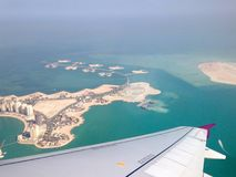 Flying over Doha, Qatar. Top view from the plane on the wing and stock photos