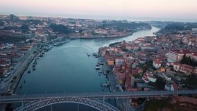 Flying over Dom Luis I iron bridge across Douro river early morning in Porto, Portugal. Aerial view of the old city center. stock video