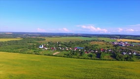 Flying over the farmland. With cultivated fields and village with a church stock footage