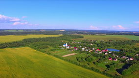 Flying over the farmland. With cultivated fields and village with a church stock video