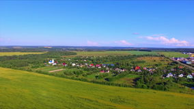 Flying over the farmland. With cultivated fields and village with a church stock video footage