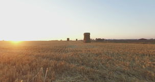 Flying over field with stacked hay bales stock video footage