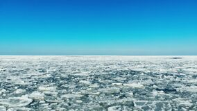 Flying over floating sea ice on sunny day. 4k stock video footage