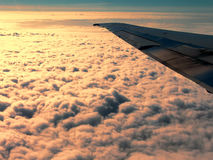 Flying over fluffy clouds at dawn. Royalty Free Stock Photo