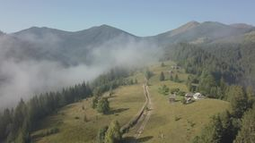Flying over fog and clouds in Carpathians mountains near by Dzembronya village, Ukraine. Panoramic view to Carpathians mountains with fog and clouds near by stock video