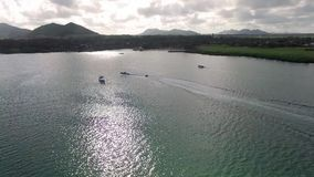 Flying over the golf field in Mauritius. Indian Ocean and beach is below. Yacht and boats on coastline stock video