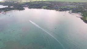 Flying over the golf field in Mauritius. Indian Ocean and beach is below. Yacht and boats on coastline.  stock video