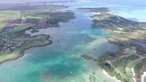 Flying over the golf field in Mauritius. Indian Ocean and beach is below. Yacht and boats on coastline.  stock footage