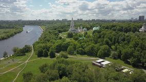 Aerial view of Kolomenskoye with Church of the Ascension, Moscow. Flying over green areas of Kolomenskoye on the bank of Moskva River with sailing boats. Scene stock video footage