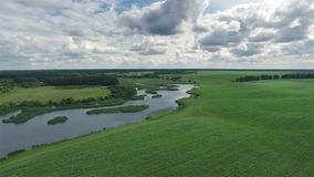 Flying Over Green Field and River. Aerial shot: Flying Over Green Field and River stock footage