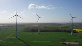 Flying over green fields with wind turbines stock video footage