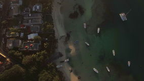Flying over housing on the coast and boats in lagoon. Aerial view of houses on the coast of Mauritius Island. Yachts and boats in clear blue water of lagoon stock video