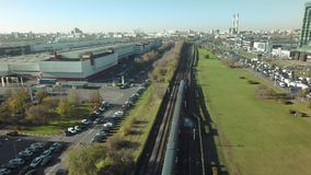An industrial city area. Flying over an industrial city area with its buildings, parkings and a train riding on rails down the middle stock video
