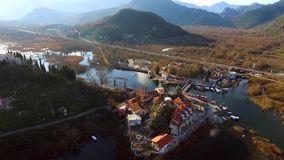Flying over the lake and the old town Virpazar, Skadar Lake in Montenegro stock video footage
