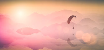 Flying over the mountain lake. Instagram stylisation. Paraglide silhouette over the mountain lake, reflected in water. Light of sinrise. Instagram stylisation Royalty Free Stock Images