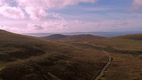 Flying over the mountain pass road on the top of Quiraing from Staffin to Uig - Isle of Skye, Scotland. United Kingdom stock footage