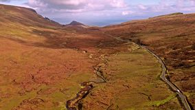Flying over the mountain pass road on the top of Quiraing from Staffin to Uig - Isle of Skye, Scotland. United Kingdom stock video
