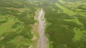 Flying over a mountain stream. Waterfall stock video footage