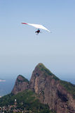 Flying Over Mountains. Handglider flying over Rio de Janeiro's landmark mountains Stock Photo