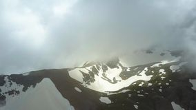 Flying over the mountains in the clouds. Mountains aerial view from drone. Aerial shot stock footage