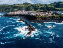 Flying over the ocean surf on the reefs coast in Maia city of San Miguel island, Azores. Flying over the ocean surf on the reefs coast in Maia city of San royalty free stock photography