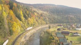 Flying over river Prut and train railways in Carpathian Mountains stock video