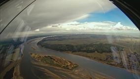 Flying over the river under the clouds. View from the cockpit IL-76. Flying over the river under the clouds. Russia stock footage