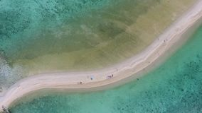 Flying Over Sandy Beach Spit. Amazing View from Above on Coral Reef and Sunbathing Tourists. Tropical Lagoon Aerial HD stock footage