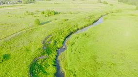 Flying over a small river, a stream flowing through the floodplain green meadows of a rural place in summer stock video