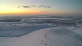 Flying over the snowfield in the evening stock footage