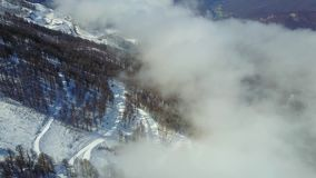 Flying over snowy mountains, forest and ski trail in fog stock video