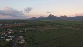 Flying over the Tamarin in Mauritius. Evening landscape with mountain and Indian Ocean in Background stock video