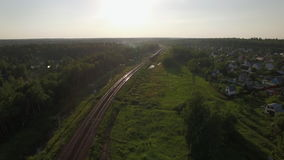 Flying over train in the countryside, Russia. Aerial view of passenger train running through the village in Russia stock video footage
