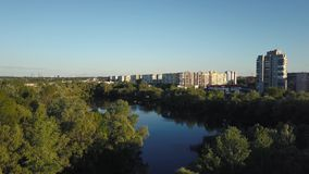Flying over the trees and lake in the city at dawn - aerial videotaping. Flying over the trees and lake in the city at dawn - aerial survey stock video