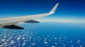 Plane wing over beautiful ocean spotted with clouds. royalty free stock photos