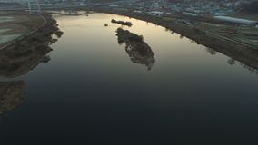 Flying over and vacant field and river with a small island stock footage