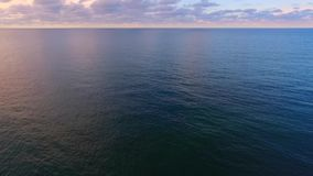 Flying over water. To fly above the surface of the ocean or sea. Clouds in the sky on the horizon. Smoothly quietly flying over the dark blue sea ocean stock video footage